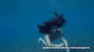 Julia is swimming underwater nude in the sea