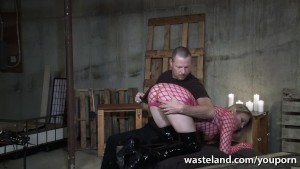 Blonde sex slave in fishnet dress gets spanked and flogged by her Master